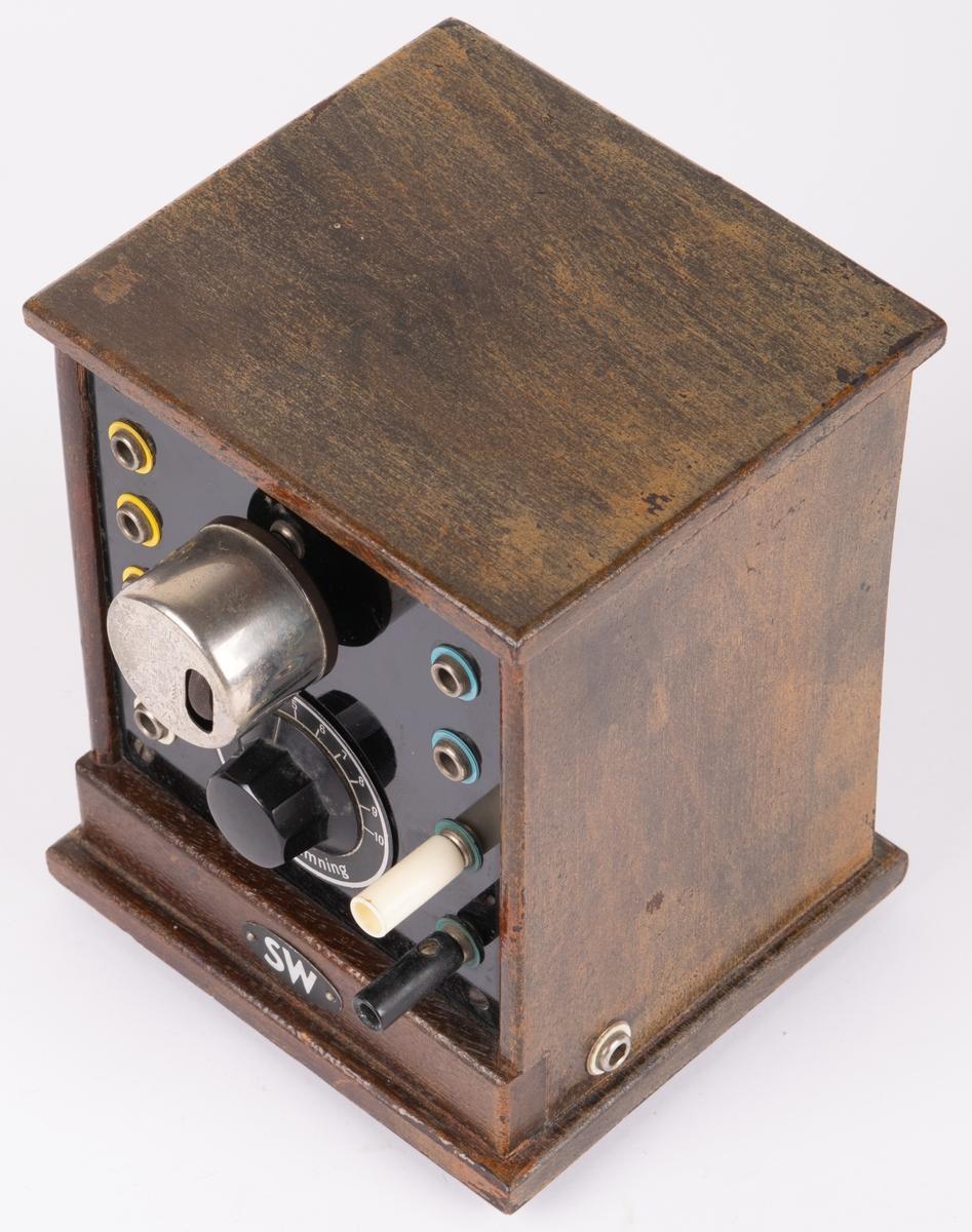 """Kat.kort: Stående vågmeter. Brun trälåda med svart framsida i konstmaterial. På framsidan avstämningsvred samt rörligt hjul """"Harlie-Detector"""". Åtta uttag för banankontakter. Oval skylt nedtill: """"SW"""". Skylt på ena sidan: """"SACHENWERK TYPE RDN TELEFUNKEN-LIZENZ."""" På undersidan pappersetikett med instruktion."""