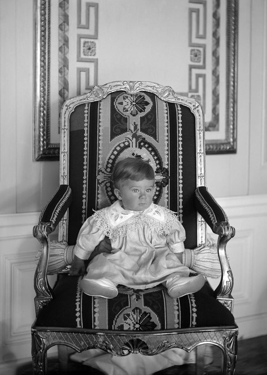 """Lille gossen Carl Philip Bonde sittandes i den så kallade """"Kungastolen"""" på godset Thorönsborg i Sankt Anna socken. Son till Philip och Anna Bonde, född Mörner och barnbarn till grevinnan Ebba Mörner. Tittar man efter noga ser man hur ett par händer hjälper till att stötta upp den lilla pojken."""