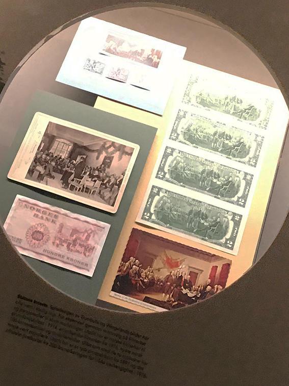 Foto av gjenstander i monter i utstillingen der de to maleriene er motiver på postkort, sedler og frimerker.