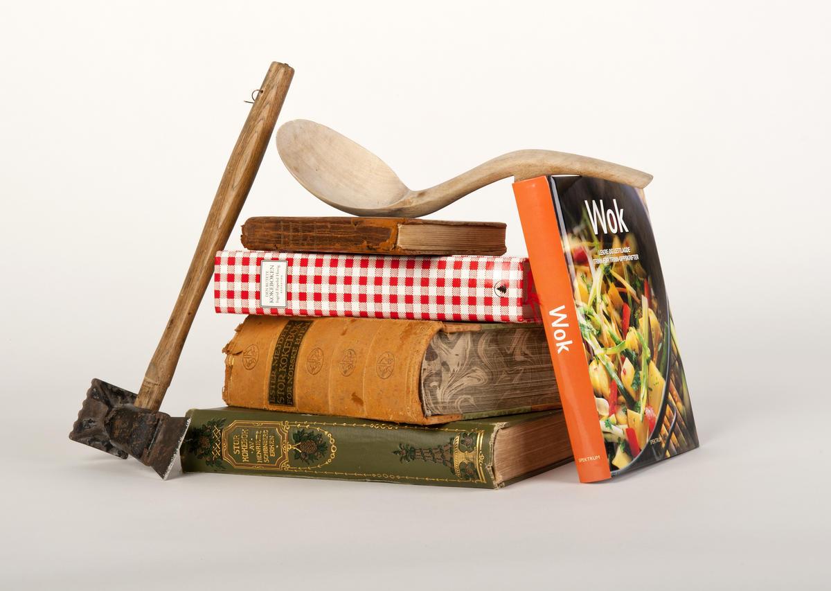 Kokebøker i stabel med kjøkkenredskaper rundt.