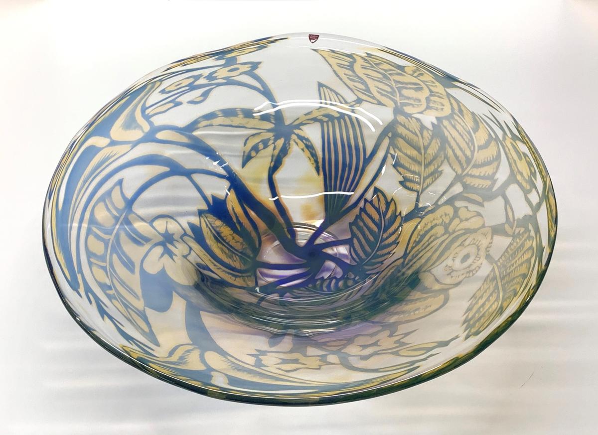 Graalfat på klack med växtmotiv i blått och gult mot en ofärgad botten. Orreforsetikett i vinrött med vit orre. Formgiven av Eva Englund.