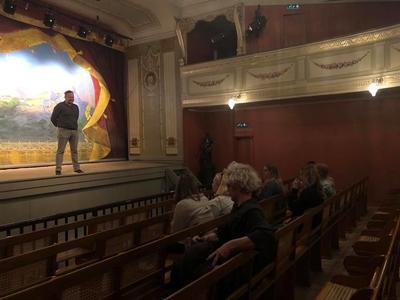 Viser formidler på teaterscenen som snakker til vidergående elever som sitter i salen. Foto/Photo