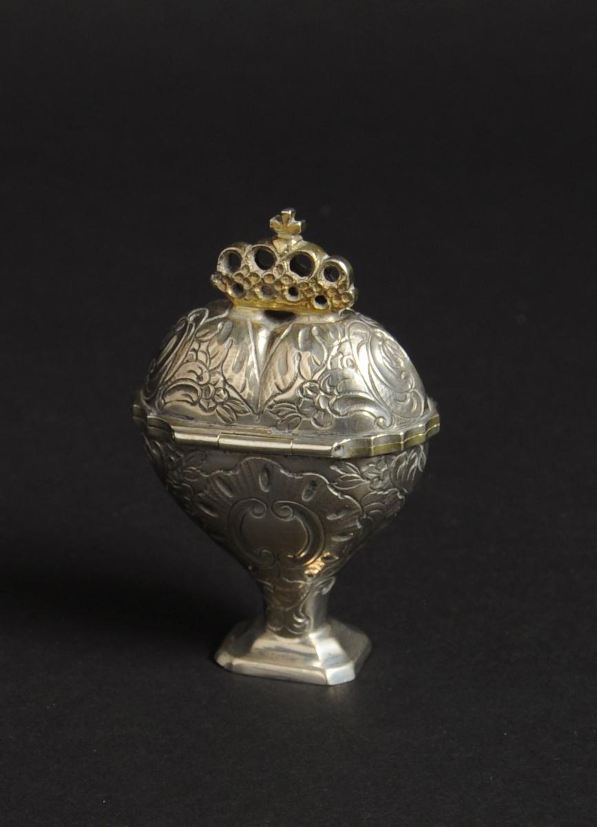 Svampehus av sølv, med hengslet lokk. Svampehuset har hjerteform med sokkel nederst, og en gjennombrutt krone øverst. Svampehuset har siselert dekor av blomsterslynger og barokkskjold.