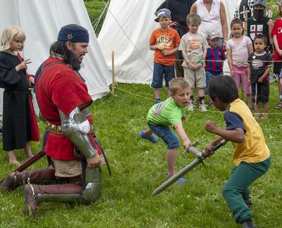 Ridder i middelalderdrakt og delvis rustning kneler mens han instruerer to gutter til å slåss med sverd.. Foto/Photo