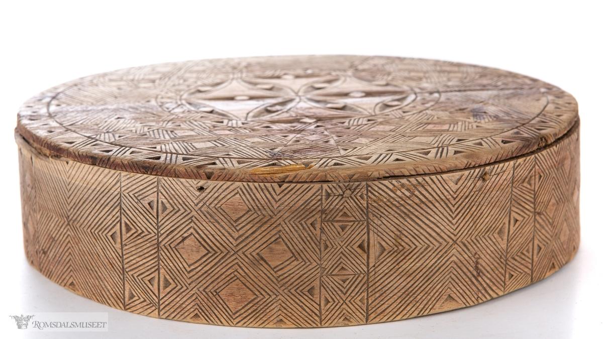 Seksbladsrose i karveskurd sentralt på lokket med dekorfelt med V-border med doble kanter. Trosk og topp er dekket med fiskebensmønster, stolper med V- former og diamantformer.