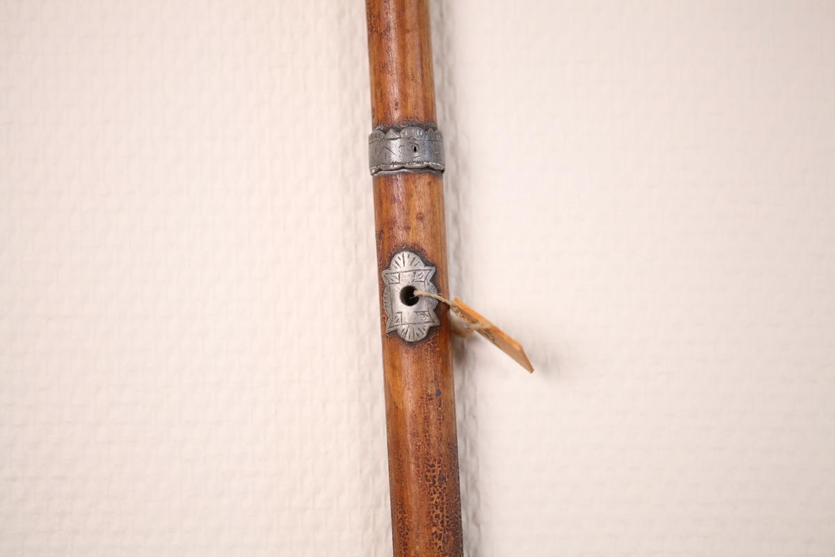 Omtalt som kirkestokk. Sølv eller tinnbeslag øverst og en ring rundt, litt ovenfor midten. Et hull er laget gjennom stokken og rundt hver åpning er et beslag av sølv/ tinn som er dekorert.