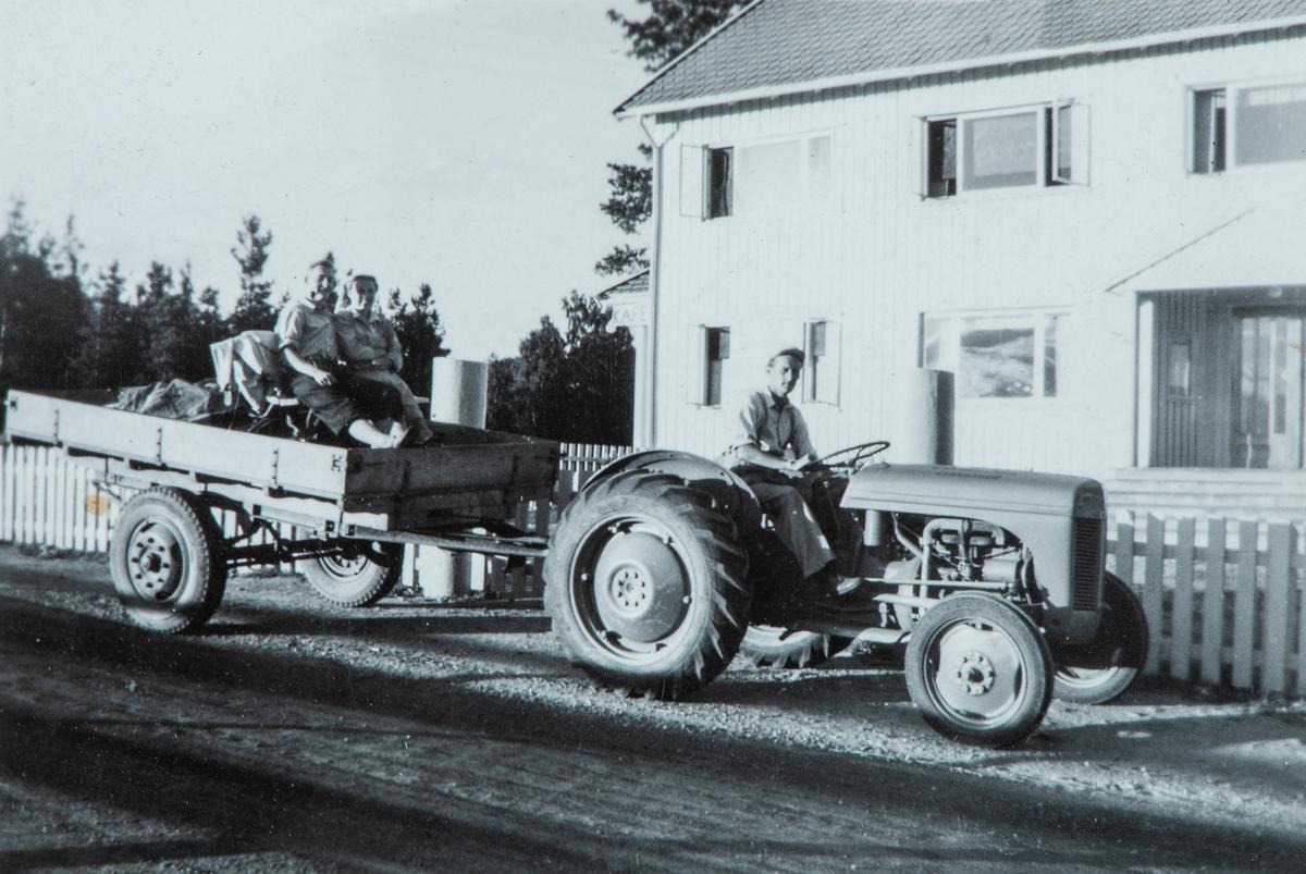 Erik Murstad på sin traktor. Her stanser han utenfor trygdekassens vindu. To personer sittende på en benk på tilhengeren.