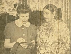 Två kvinnor tittar tillsammans i en skrivbok. Kvinnan till v