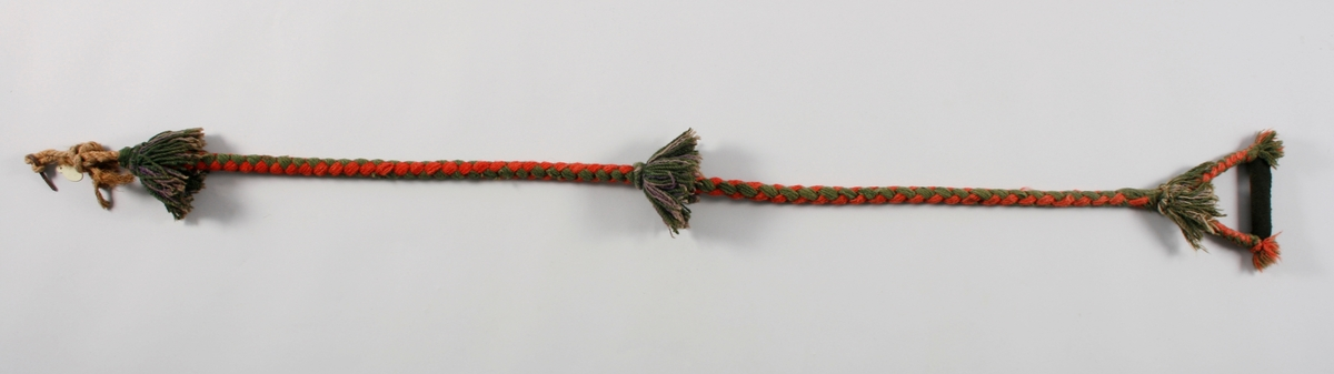 Sengebånd,reip av hamp, rundt reipet er det flettet rød og grønn ulltråd. I enden deler bandet seg i to og danner en hempe med en trepinne trukket med sort ulltøy for håndgrep i midten. Øverst, nederst og på midten er det dusker i grønt og lilla ullgarn.