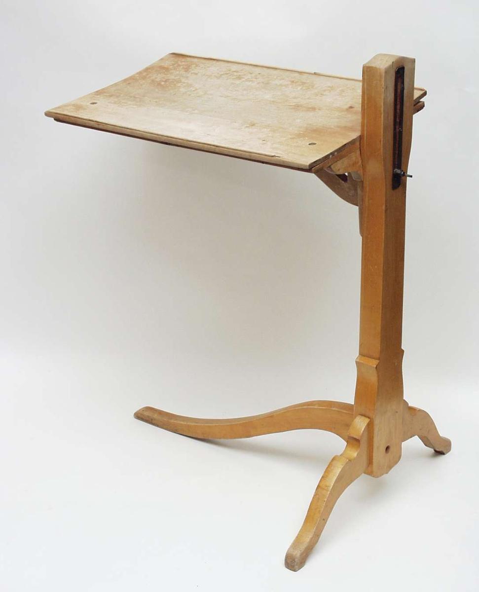 Bordet har plate med opphøyde kanter og stolpe med høydeskyver. Bordet har tre ben, to korte og ett lengre som følger bordlengden.