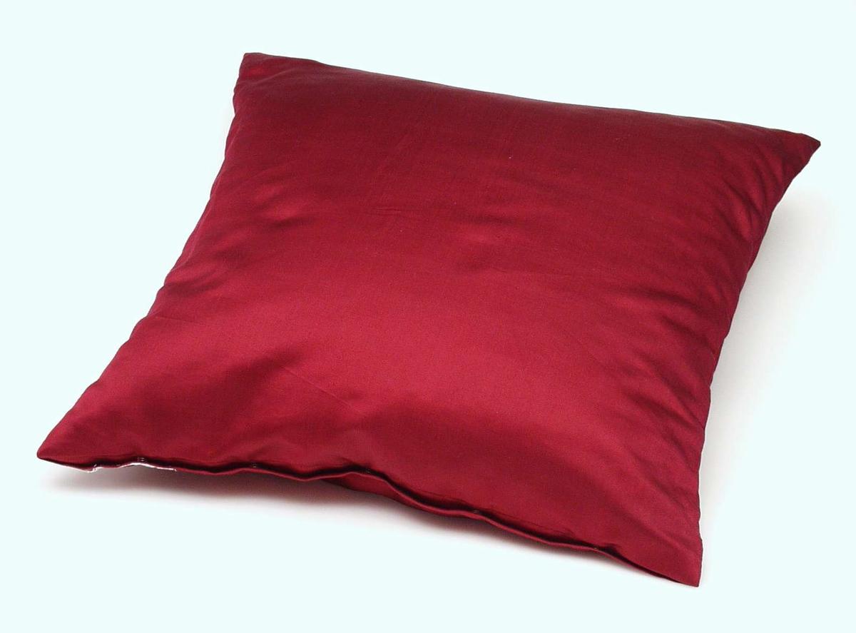 Pute trukket med rød silke. Søm i begge sider og lukning med fem trykknapper. Fyll av god kvalitetsdun.