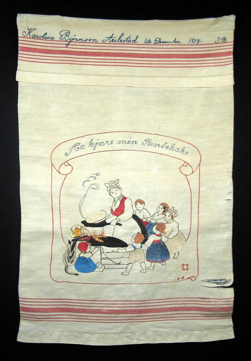 Kone med skaut, panne i hånden, pannekake, åpen ild, kaffekjel, katt og seks barn rundt hvorav en sitter på gulvet. Stilisert blomst i hjørnet.