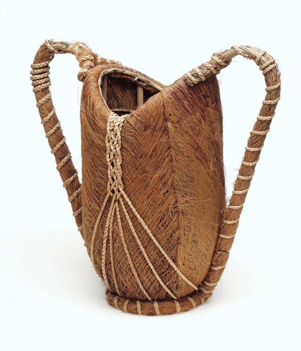 Kurv i kokosbast med urnefasong. Den har to hanker, neverbunn, rundt fotstykke, bastflettning om hank og fotstykke.
