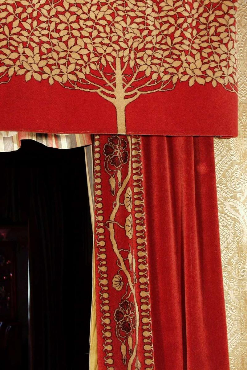 Hovedfargen er mørk rød. Langs kanten mot døråpning en 16 cm bred bord i grått og svart på rød bunn. Motiv: bølgete gren med blomster og blad. En rapport: 45 cm. Fôret med rød bomullskypert, stramt holdt, for å holde fasong på portieren. Øverst i sydd fem metallringer ved fold. Kappe: 19 cm bred oppbrett av plysjen. Øverst isydd flere metallringer hvor det er tredd en tykk ståltråd i gjennom og festet til et brett. Motiv: 5 trestammer opp til forgreninger og et rikt løvverk i grått og svart på rød bunn som en sammenhengende horisontal bord. Plysj av meget fin kvalitet. Ullen eller hårene av ukjent dyrerase; blanke, spenstige, jevne. Plysjvev, maskin innknytt-innvevd oppstående lo i flere farger etter hullkortsystem, antagelig jacquardsystemet på en to-skafts bunn.