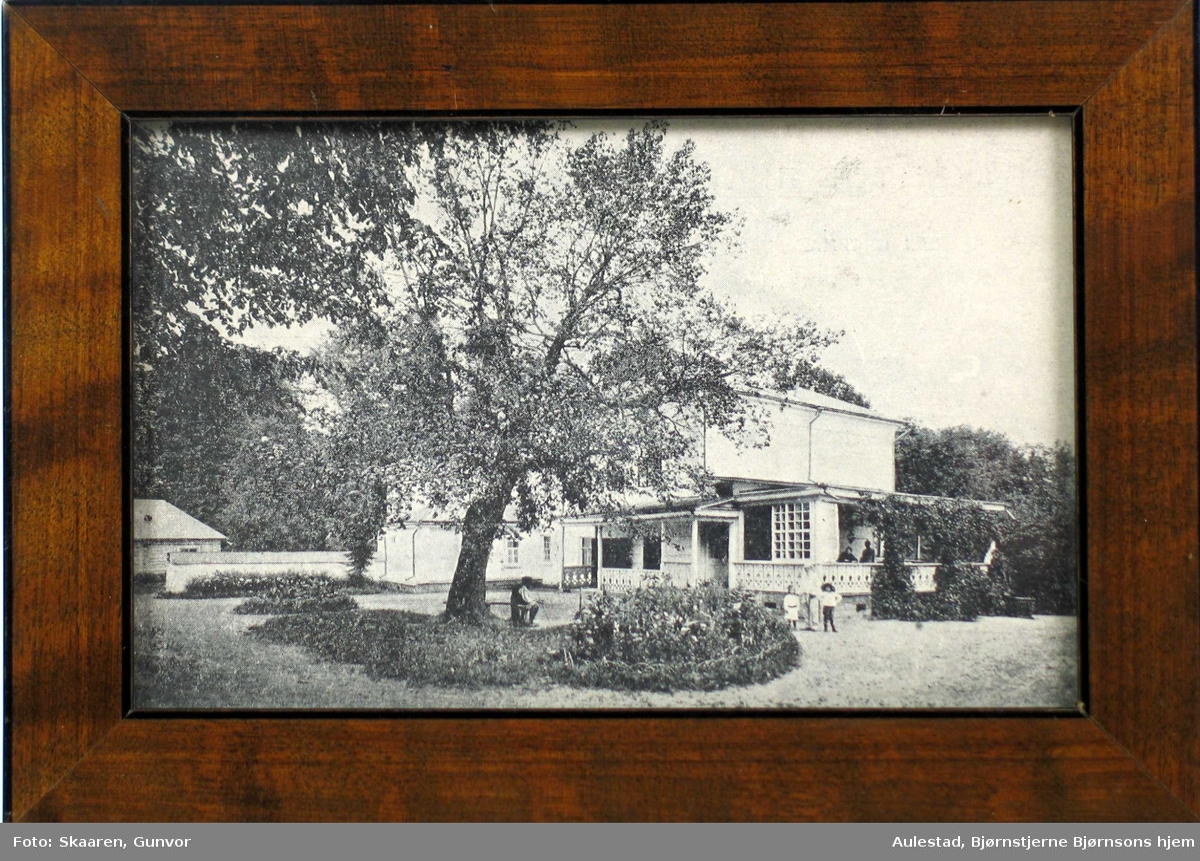 Hus med hage. To personer på verandaen, to barn i hagen og en mann som sitter på en benk under et tre.