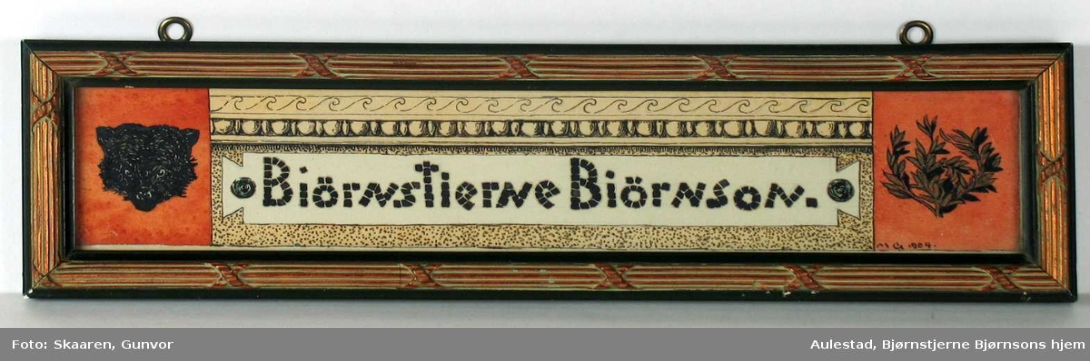 Bjørnstjerne Bjørnson i mosaikskrift på hvit bunn. Øverst frise løpende hund, så perlestav og selve navnet omgitt av prikket bakgrunn. Til venstre bjørnehode på rød bunn, til høyre laurbærkrans på rød bunn. Innrammet i grønn treramme med opphøyet forgylt dekor.
