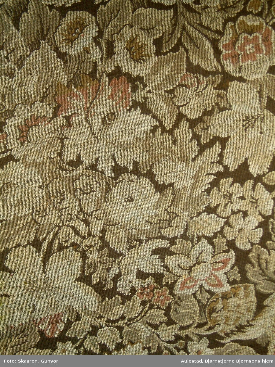 Maskinvevd møbelstoff med blomstermotiv i beige, brunt og rødt. Stykket er rektangulært, satt sammen av to store deler og påsydd kant/sider i samme materiale.