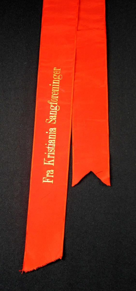 Begravelsessløyfe i rød silke med gullskrift.
