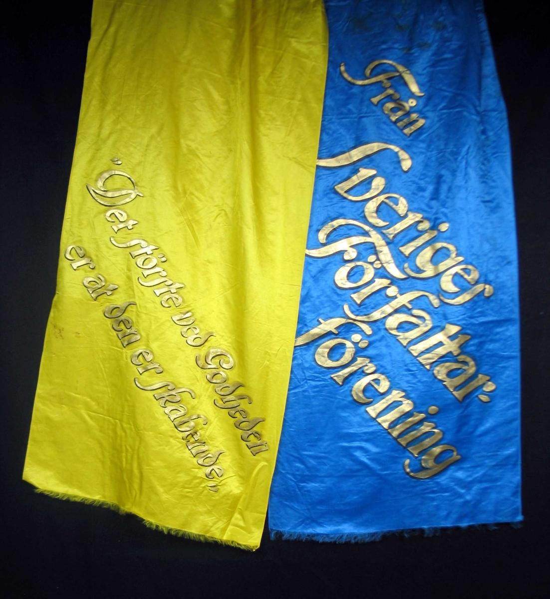 Begravelsessløyfe i gul og blå silke med tekst i gull.