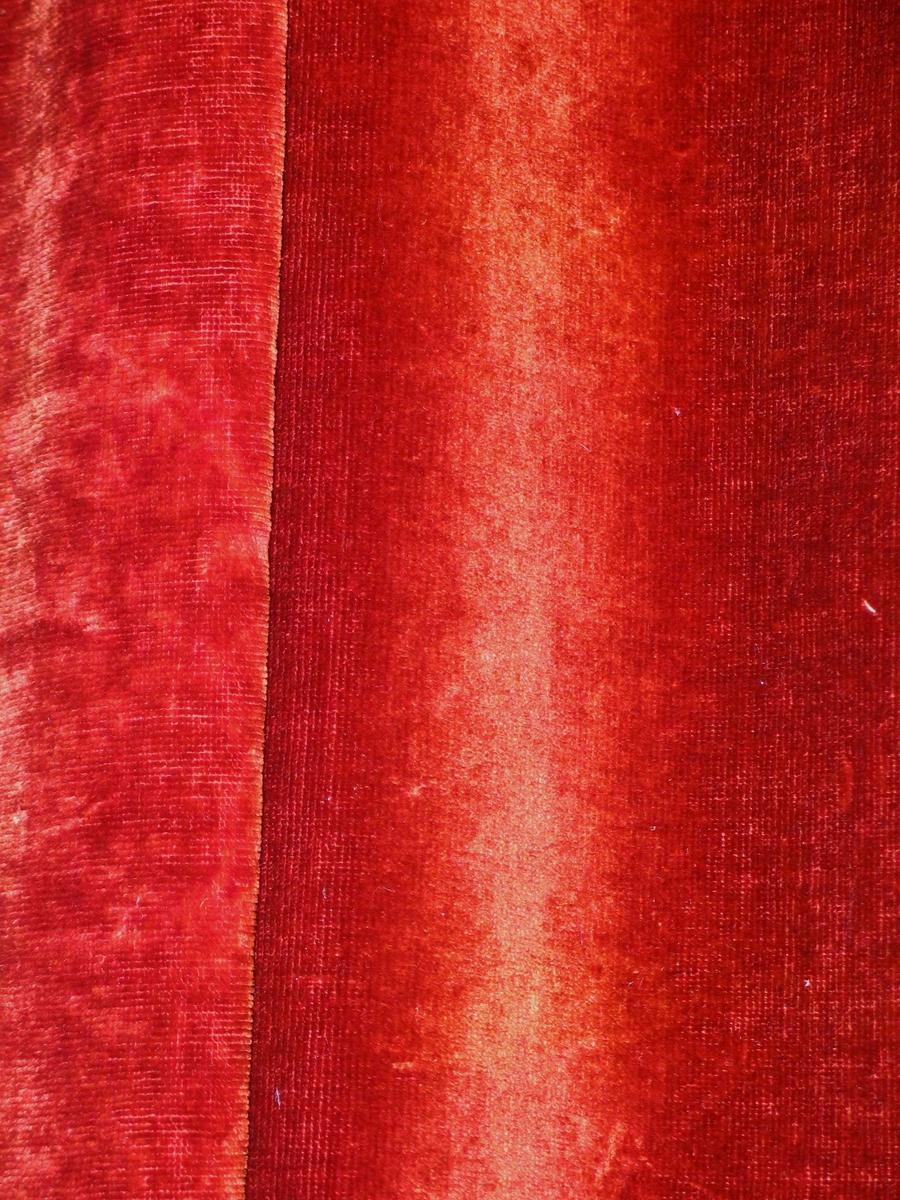 Rødbrun portiere i bomullsplysj foret med grønn sateng.(Opprinnelig svart?). Isydd metallringer samtidig med en liten fold. Hengt på kroker i en trelist.