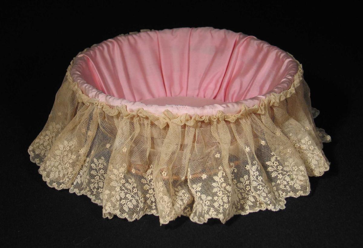 Rund kurv med trebunn foret med rosa silke og hvit fritthengende blonde drapert rundt kanten. Rosa silkebånd flettet rundt trespiler danner veggen i kurven. Sløyfer. Innhold: visittkort og avisutklipp.