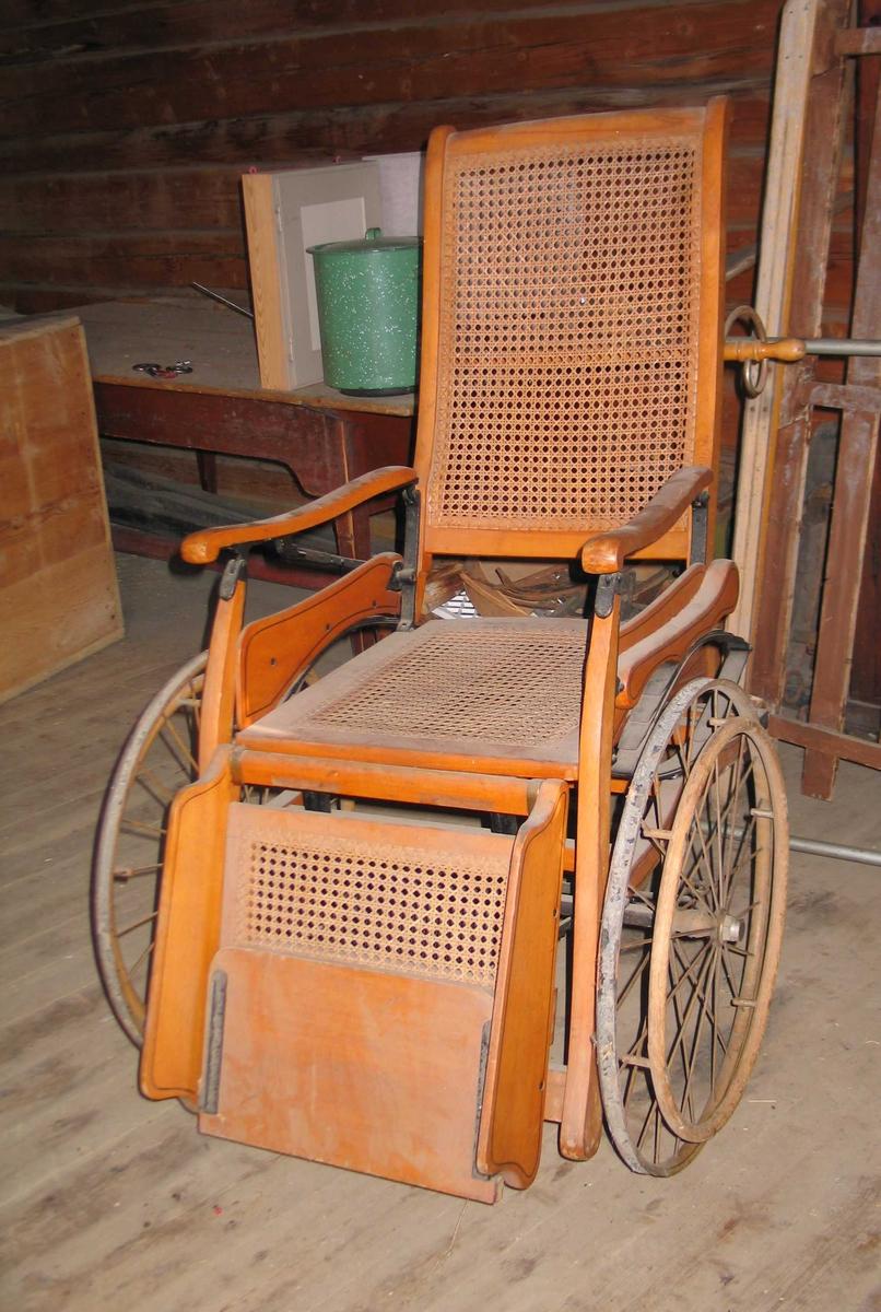 Rullestol i tre med rotting i rygg og sete. Treverket er lakkert med dekor i form av svarmalte linjer. Ryggen og fotbrettet er justerbar. Hjulene er i metall påsatt en trering ytterst. Det er også et lite hjul bak. Her er gummien inntakt. Håndtaket er en dreid profilert trestang med c-formede metallfester.
