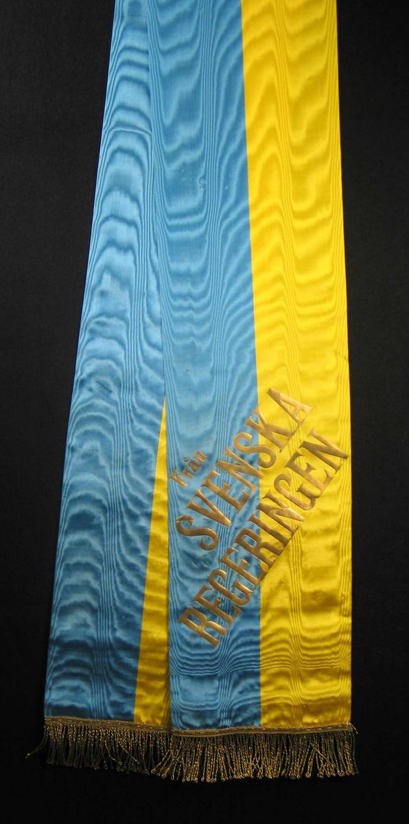 Silkesløyfe i blått og gult med gullfrynser.