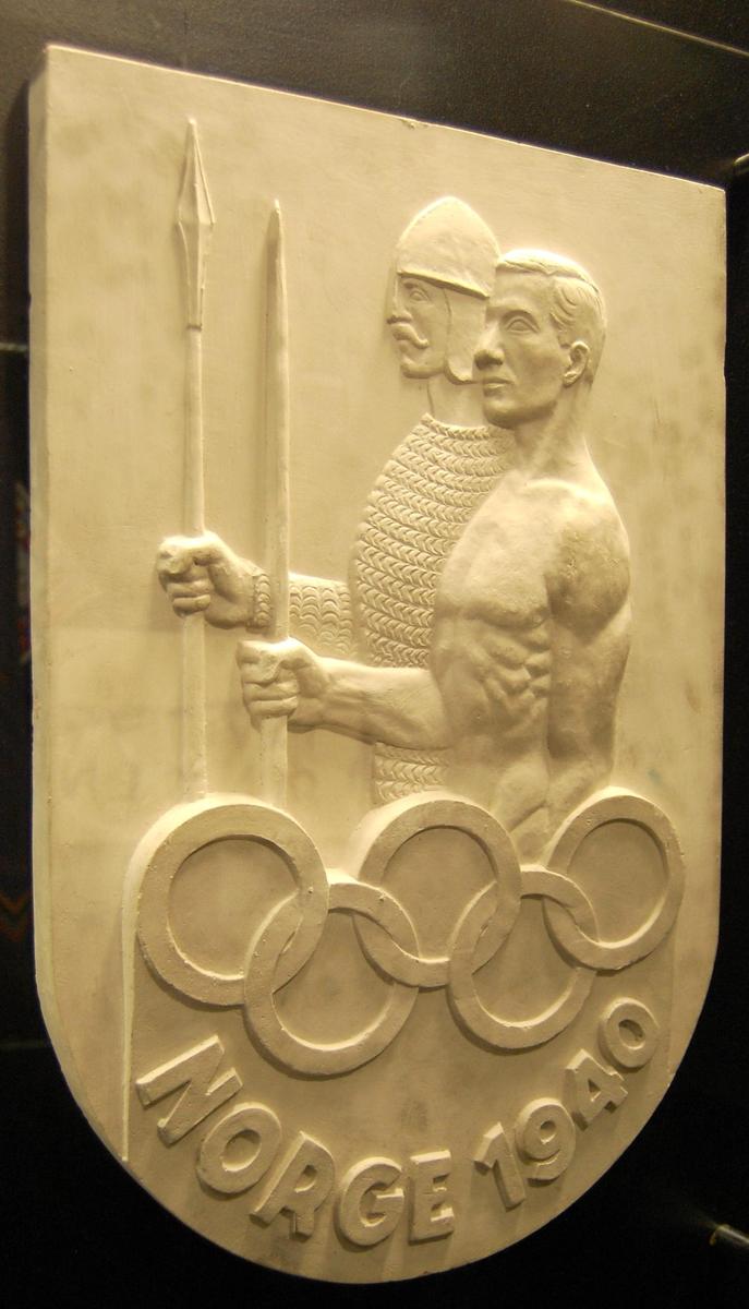 Skjoldformet plakett av gips med motiv av to menn, en i rustning og hjelm og en i bar overkropp. De olympiske ringene inngår i motivet.