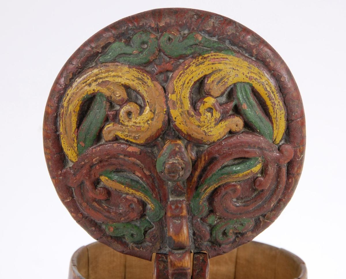 Kanne av furustaver. Lokket med gule, rødbrune og grønne akantusblader. Lokkgrepet formet som et dyrehode. Korpus med to gjorder oppe, to midt på og tre nede, tre av stavene er nederst formet som føtter, malt rødbrun.