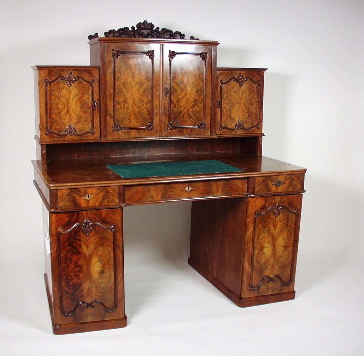 Skrivebord i nøttetre. To skapseksjoner holder pultplata, på pulten står skap. Lister på dørene er profilerte og utskjærte. Grønn filtmatte ligger på pultplata til skriveunderlag.