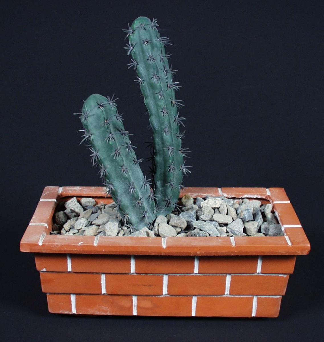Firkantet blomsterpotte i keramikk med mønster som ligner teglsteinsmur. Kunstig kaktus med stein rundt.