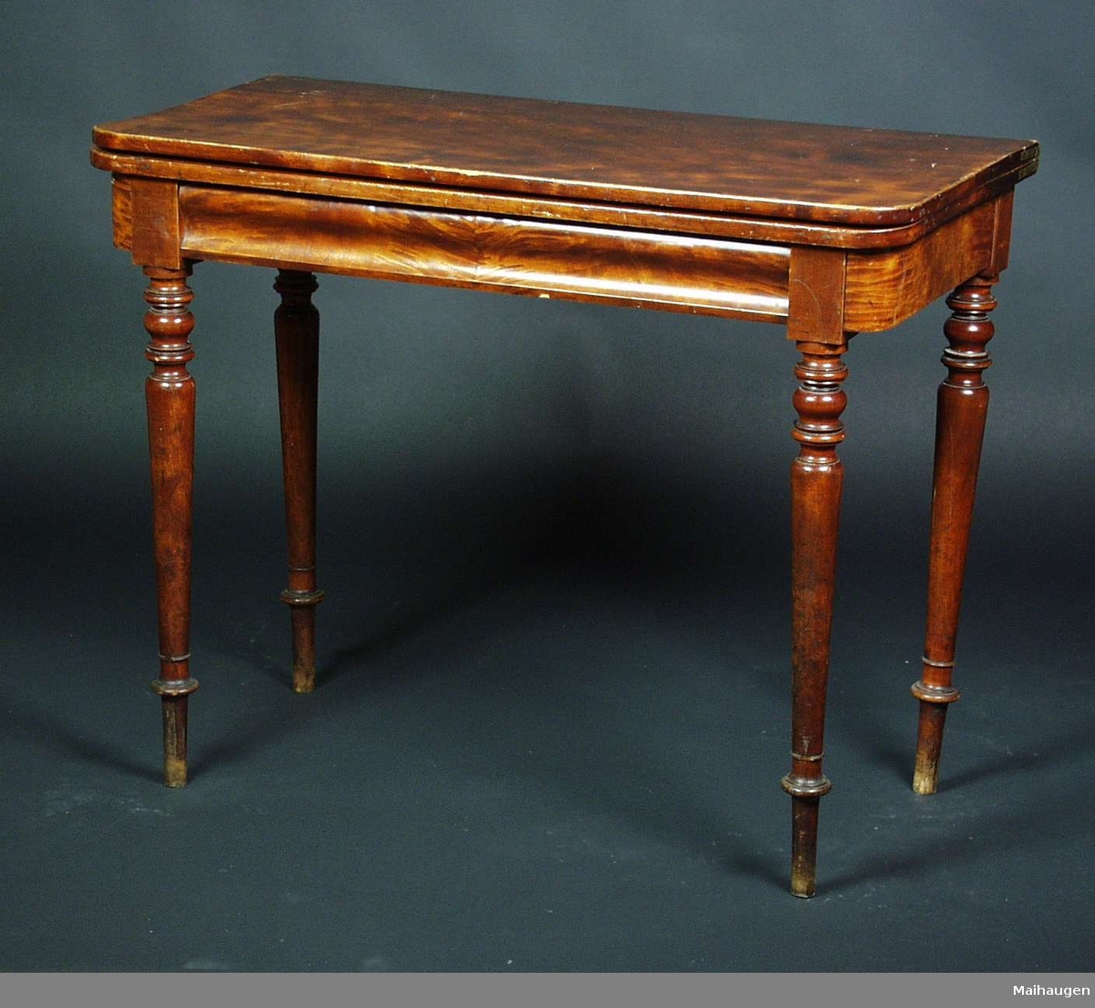 Et bord i bjørk med dreide ben. Sargen på framsiden er buede formet. Bordplaten er festet med en trebolt til sargen og dobbel, kan slåes opp til et firkantet bord. Bordet kan også stå inntil en vegg. Bordet er lakkert brunt.