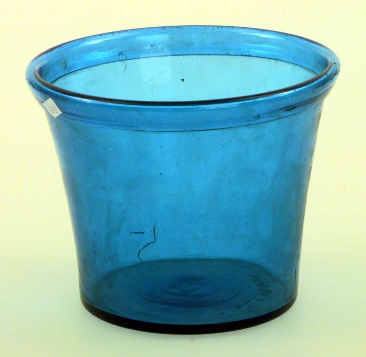 Urtepotte i blågrønt glass, ombrettet munningrand. Formen er konisk.