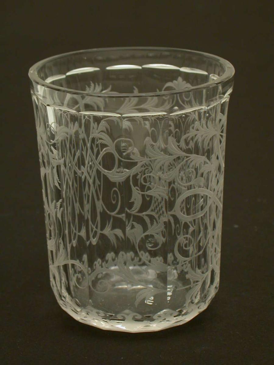 Glass med fasettslipt korpus. Overgangen mellom korpus og fot (bunn) er også slipt. Hele glasset er rikt dekorert med bladverk og bånd som slynger seg.