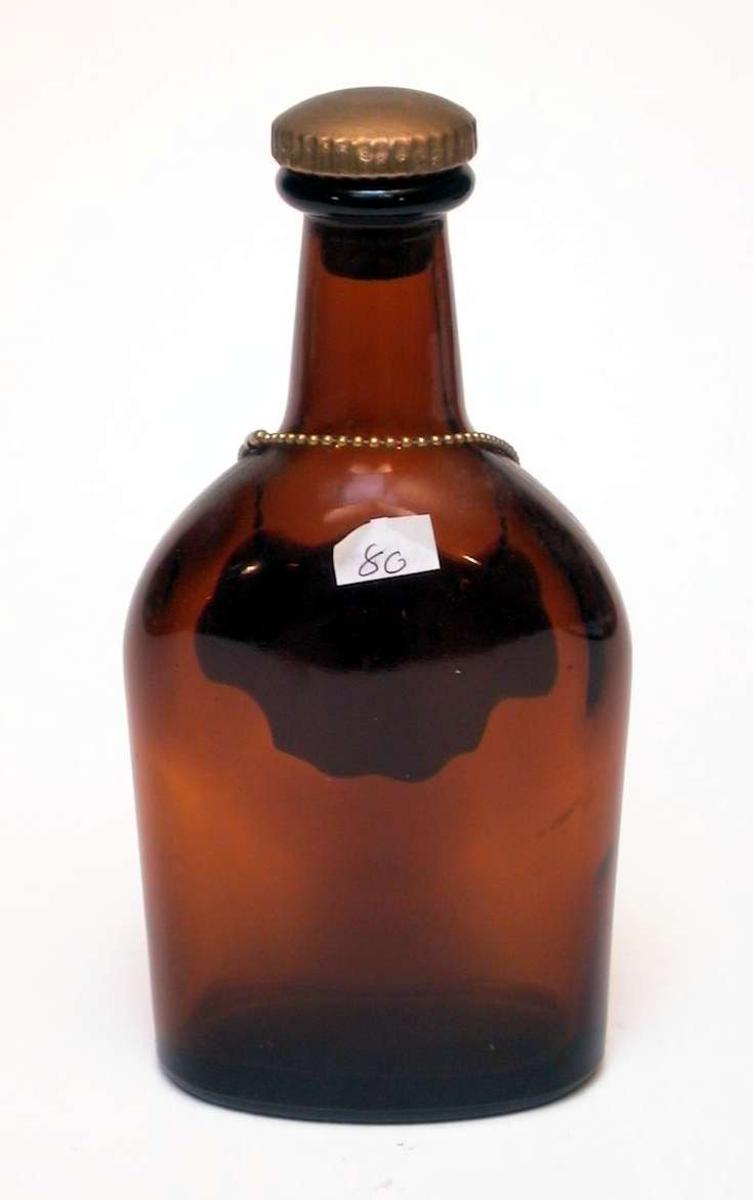 Flat brennevinsflaske i brunt glass med kork. Rundt halsen på flasken henger et skilt i lenke. Det er av hvitt glass, dekorert med blomster og er påskrevet 'Whisky'.