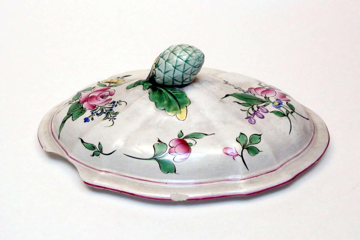 Ovalt lokk i kremfarget keramikk med polykrom blomsterdekor. Lokket er defekt. Fatet eller terrinen som lokket har hørt til, mangler.