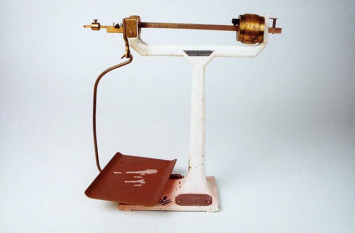 """Skilt med produsentens navn. Farge: Hvit. Stativ av støpejern. Vektarm og lodd kobberfarget. På fot et skilt: """"Tilhører Postverket. Lovlig fra 8 til 2 kg"""