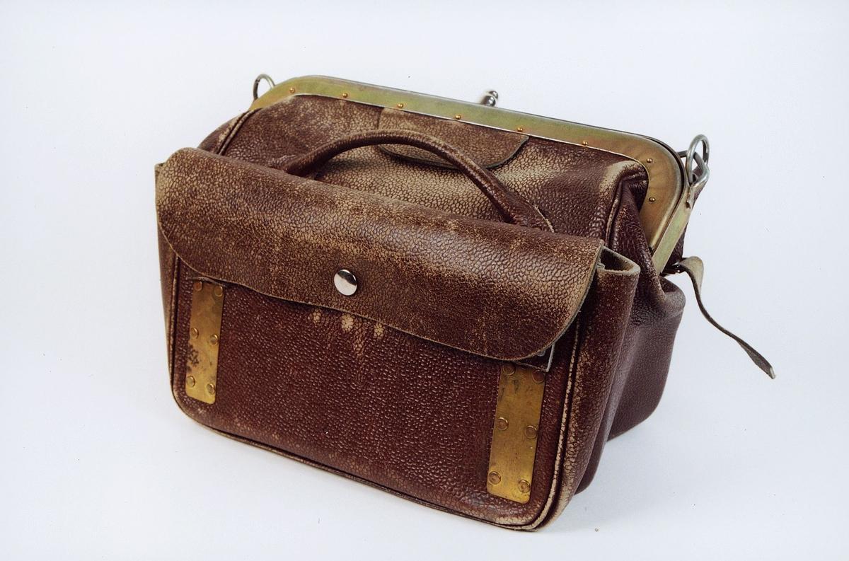 Brun pengeveske til bruk i landposttjenesten. Utstyrt for montering av myntapprat. Veska har bærehåndtak, skulderreim og utstyrt med låsanordning, og sidelomme.