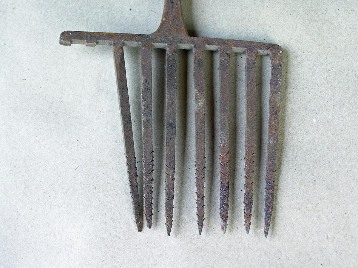 Håndsmidd gaffel som har hatt 9 tinner - 2 mangler. Tinnene har mothaker. 2 hull øverst på skaftet for feste av treskaft; sistnevnte mangler. En del rust.