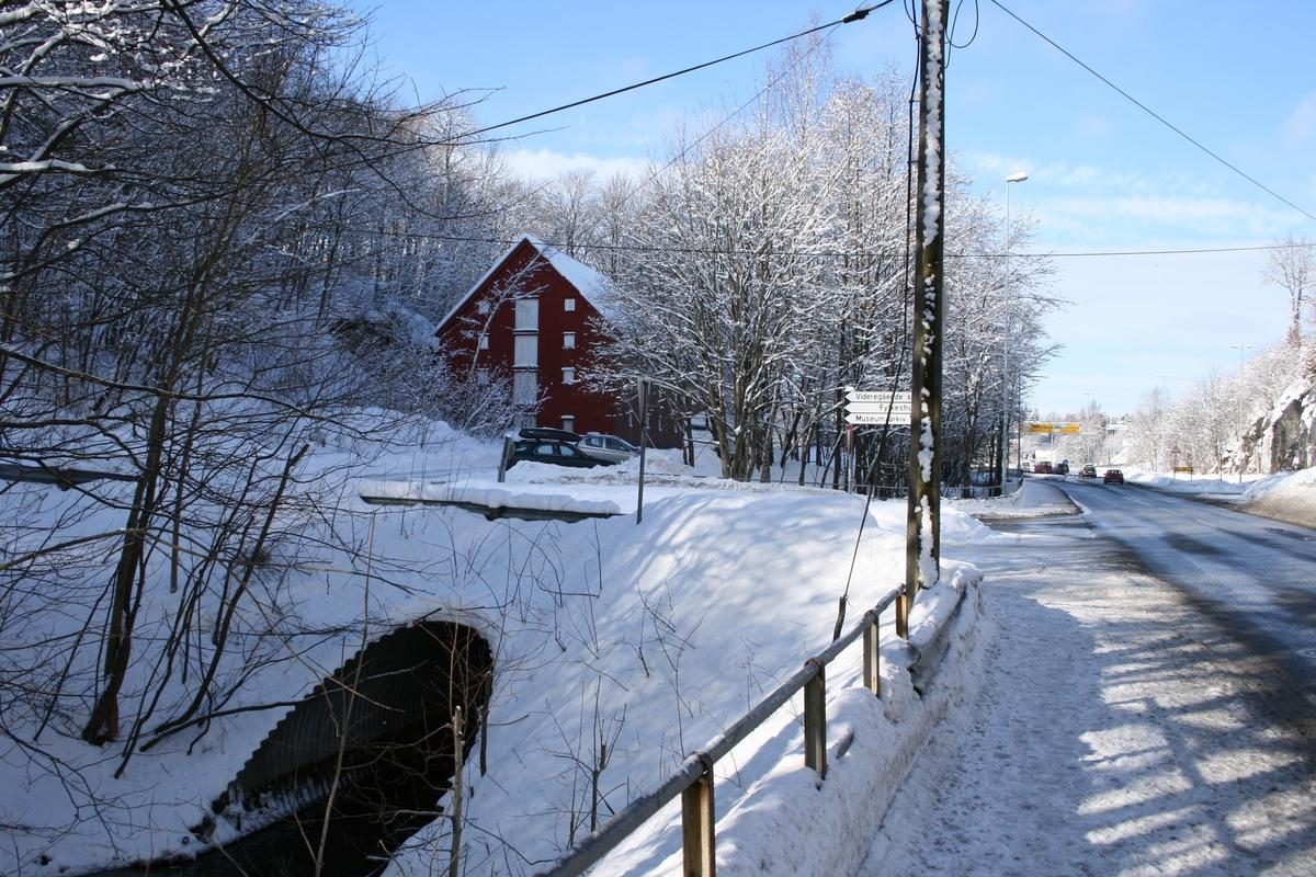 Langsæ. Ved Barbuelva, som renner i rør under Ragnvald Blakstads vei. Riksvei 410 t.h. Skilt til Videregående skole og museum og arkivs parkeringsplass. Klokkebua i bakgrunnen. Snødekket vinterlandskap.