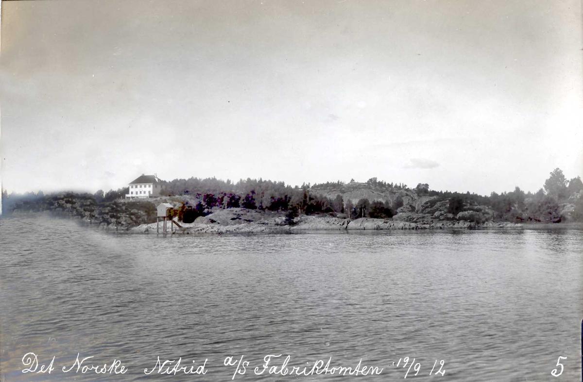 """""""19/09-1912"""" Nitriden. Direktørbolig for Smelteverket til venstre er allerede bygget. Fyrlykt nr. 612 i Norsk Fyrliste, bygd 1894, flyttet til Friisøy i 1929, står på et skjæret. Innenfor er tomten for fabrikkanleggene til Nitriden. På høydedraget til høyre høydebasseng for trykkvann. Tromøysund i forkant."""