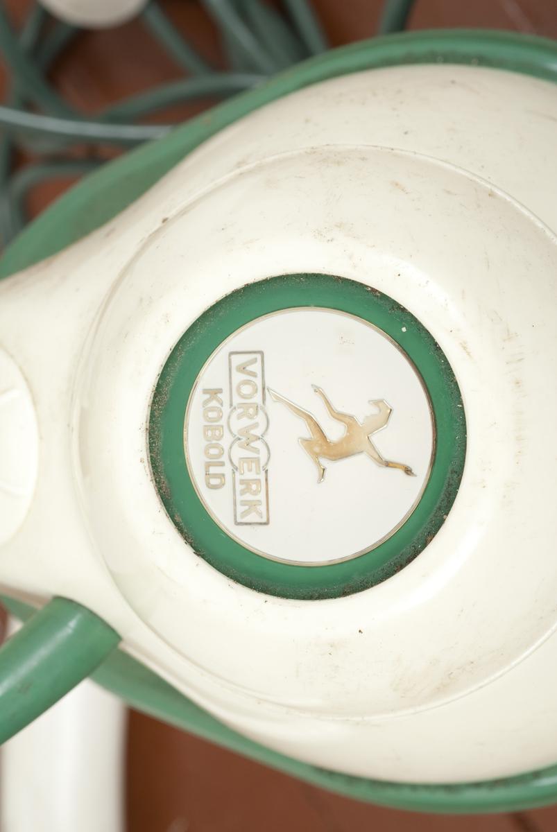 En støvsuger (A) av plast og tekstil i fargene grønn og hvit. Det følger med to munnstykker B og C til støvsugeren. Del B er kort og bred, del C er lang og smal.