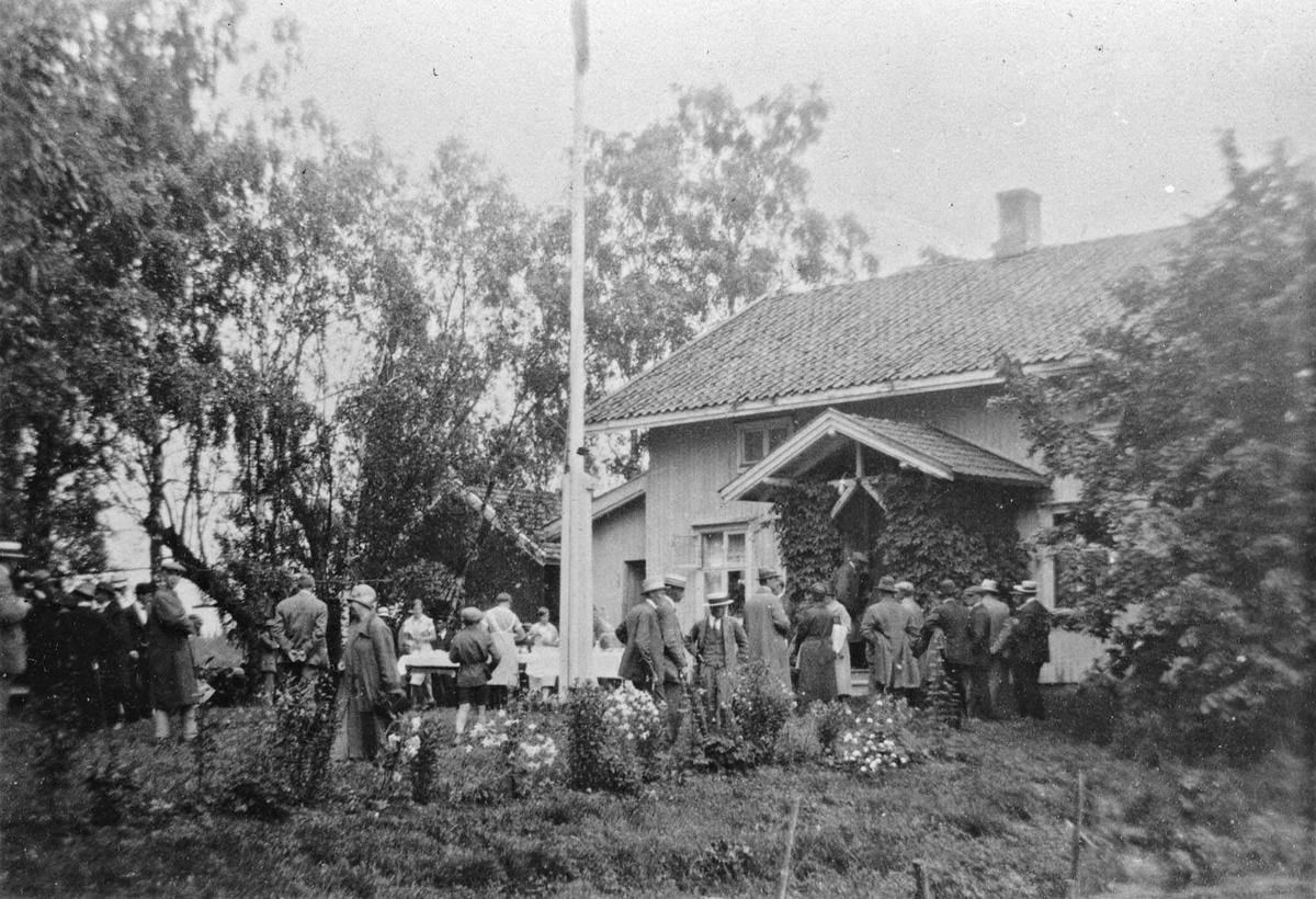 Hos gårdbruker Ruud, Enebakk. Bikongress i Enebakk, Juli 1927. Publikum samlet i hagen. Oppdekket til servering ute. Serveringspersonale i uniform. Sveitserstilhus med flaggstang.