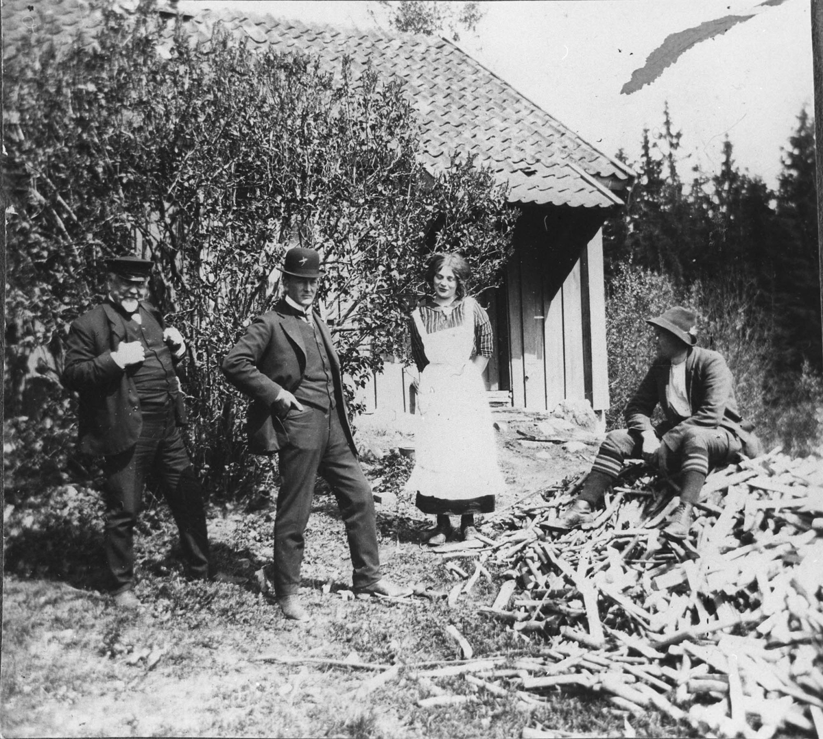 Foran uthuset. Harald Falkenberg til høyre. En sitter på ved haugen.