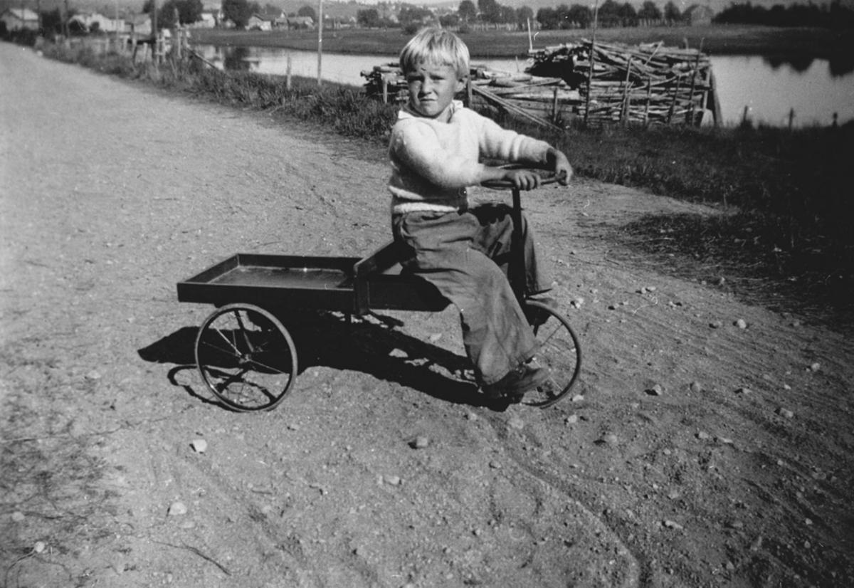 Liten gutt på trehjulssykkel med lasteplan.
