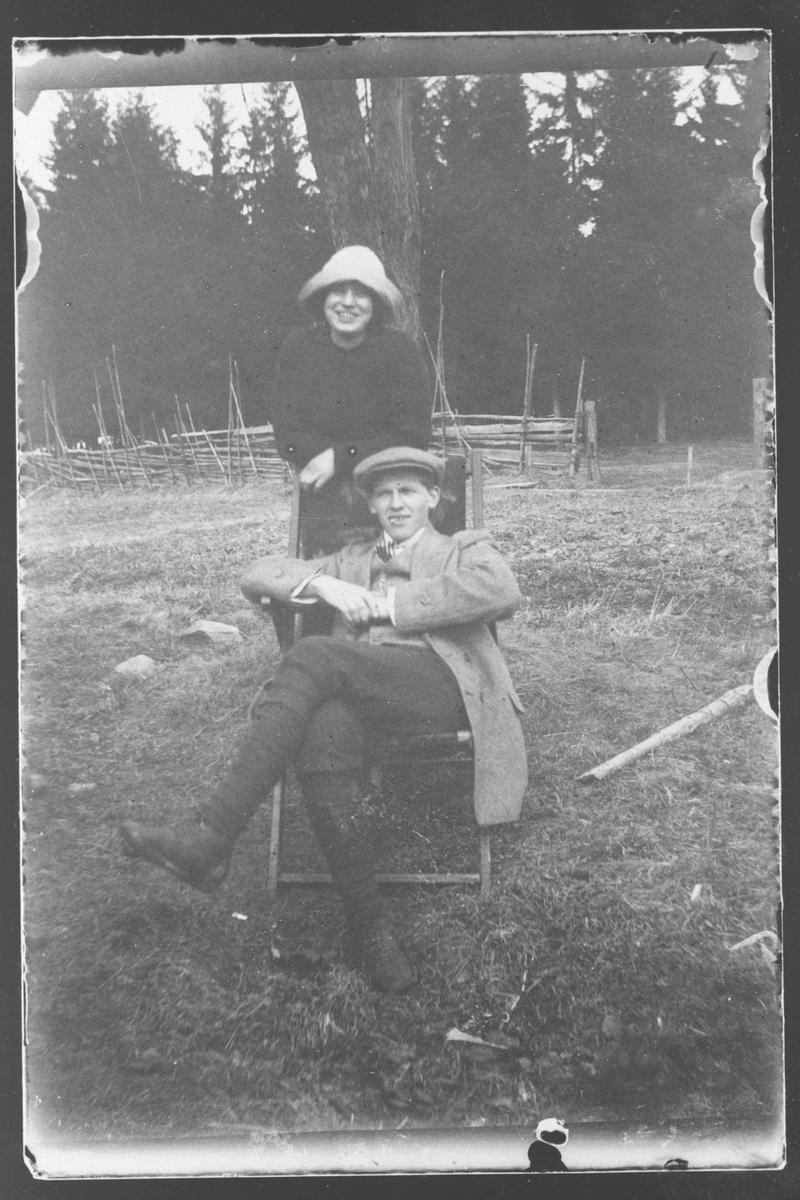 Lukennga. Mann sitter i fluktstol, kvinne står bak stolen.