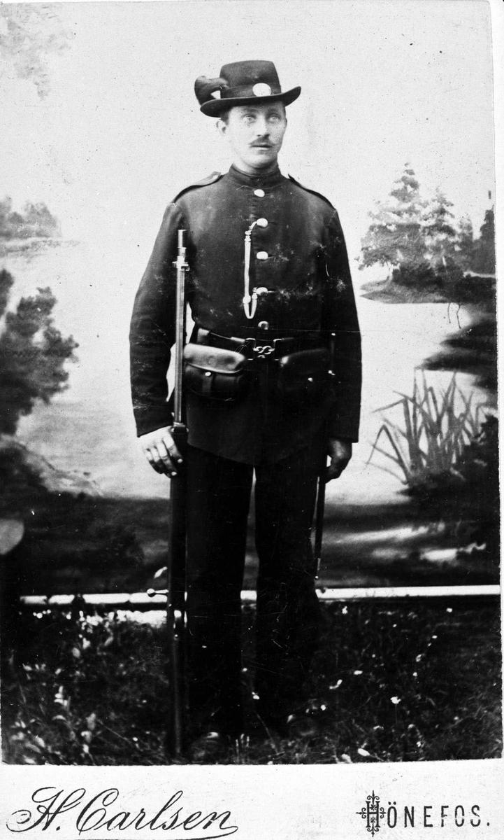 "Knut Avenstad i militær uniform som menig ved infanteriet (Musketerne), som reglementert fra 1877-1888. Hatt med ""fjær"" Studioportrett"