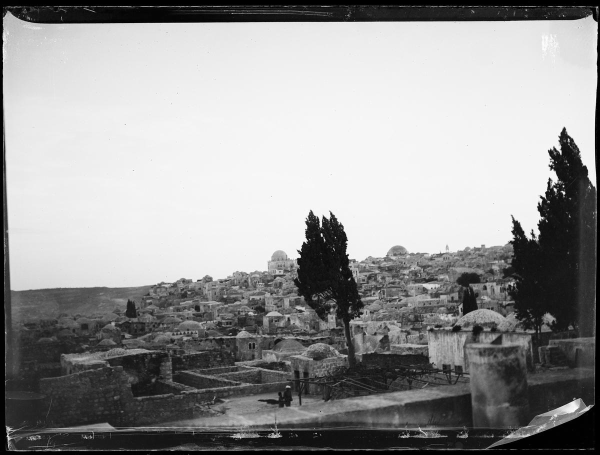 """""""Sion. Jerusalem."""" (Bildetekst fra album) Utsikt mot en landsby, med trær i forgrunnen."""