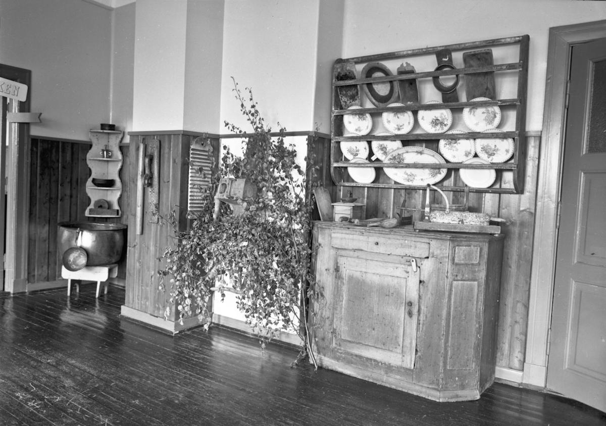 Fra bygdeutstillingen i 1955. Div. interiør: vaskebrett, strykebrett, fat, tallerkener, kaffekvern, greinkutter?, stor kjele, m.m..
