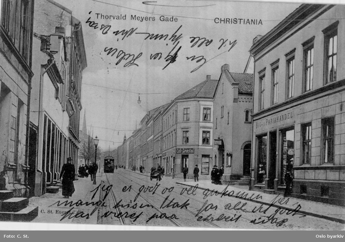 Nedre del av Thorvald Meyers gate med trikk, hestekjerre og spaserende. Butikk, café, butikkskilt. Postkort med påskrevet hilsen. datering etter 1891 (jf. tårnet Paulus kirke i bakgrunnen)